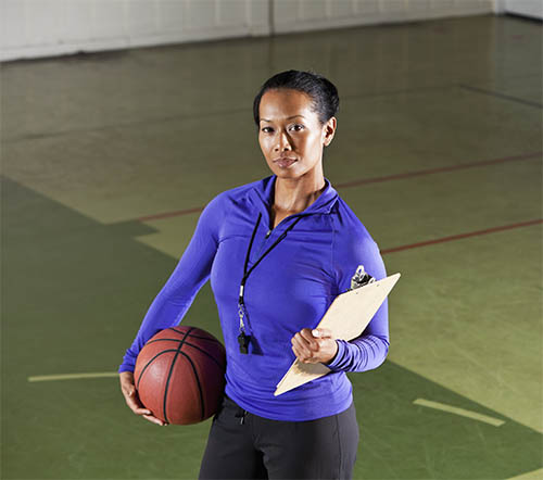 Female basketball coach holding a basketball and a clipboard